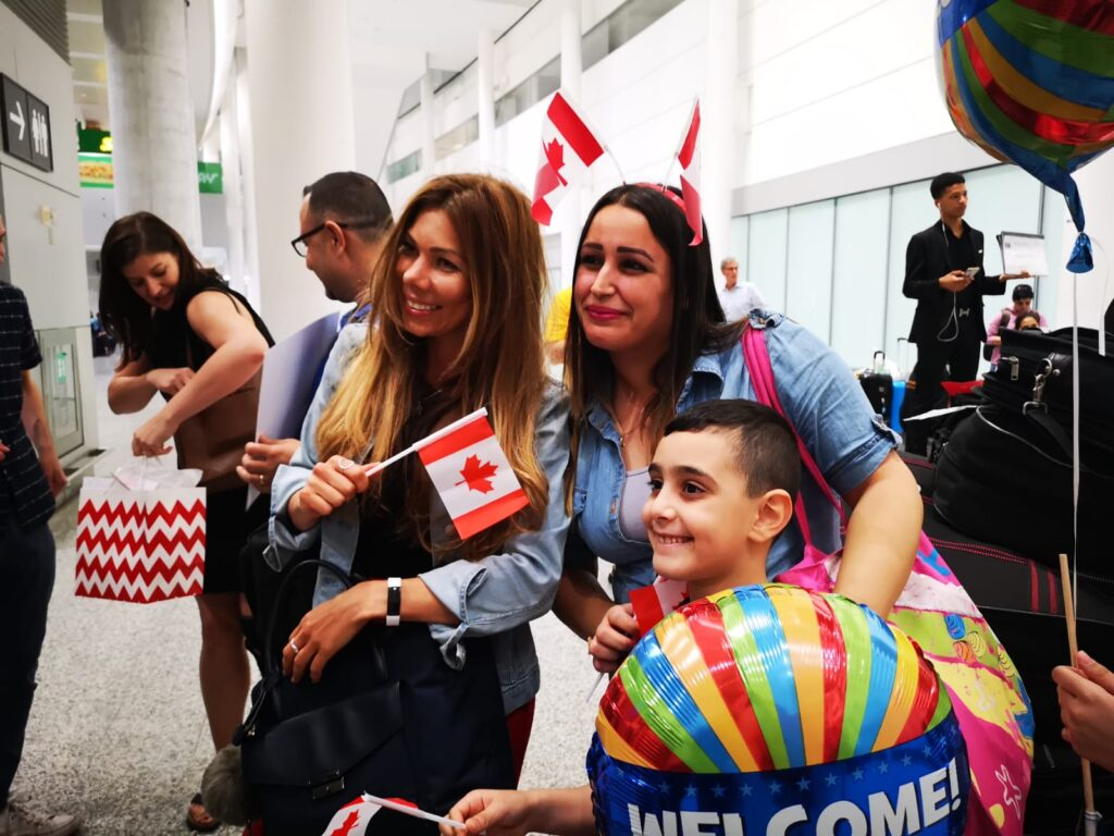 A family is greeted by new colleagues from Paramount Fine Foods in Toronto. The chef and his family arrived from displacement under Canada's Economic Mobility Pathways Project.